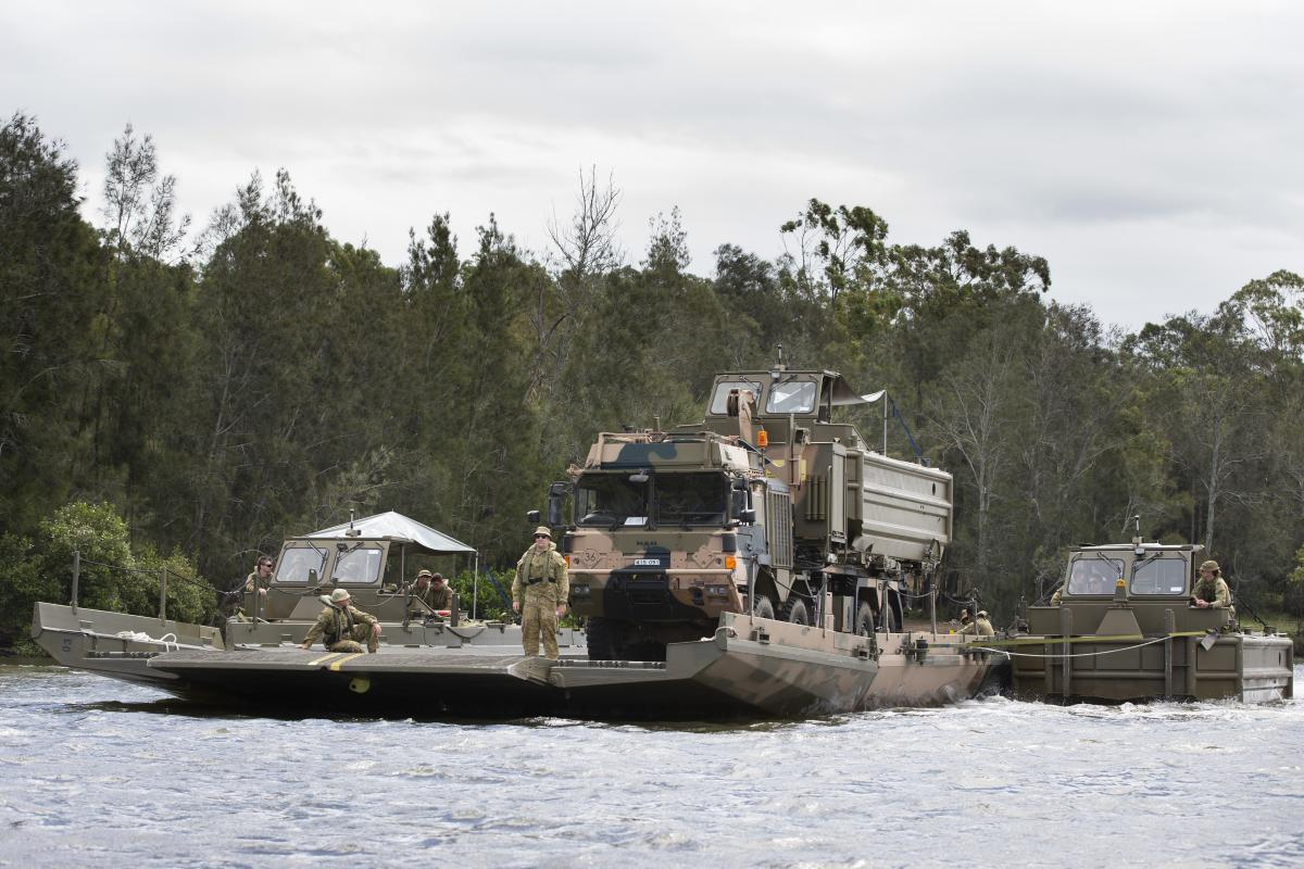 Students from the Bridge Erection Propulsion Boat course manoeuvre a bridge transporting a HX77 truck on the Georges River, Sydney. Photo: Petty Officer Lee-Anne Cooper