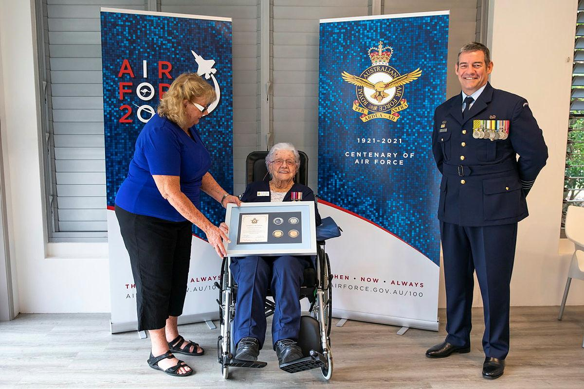 Wilma Ayles, centre, supported by her daughter Evelyn Schuetze, receives an Air Force 2021 memento from Senior ADF Officer Amberley Group Captain Iain Carty at Cooroy, Queensland. Photo: Leading Aircraftwoman Emma Schwenke