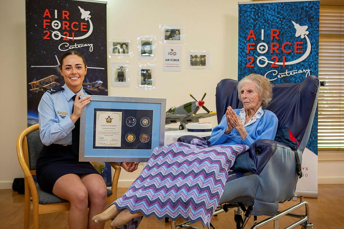 Leading Aircraftwoman Emma Singleton with the Chief of Air Force award presented to her great-grandmother Betty Howells to mark her 100th birthday. Photo: Sergeant Bill Solomou