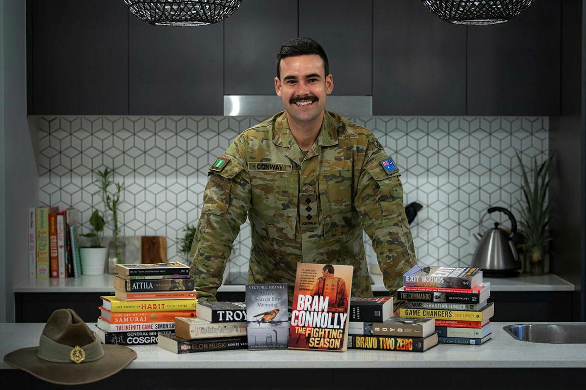 Captain Dylan Conway, of the 6th Battalion, Royal Australian Regiment, with books he read while bed-ridden after surgery. He later recommended books to others as part of his initiative, Brothers n' Books. Photo: Private Jacob Hilton