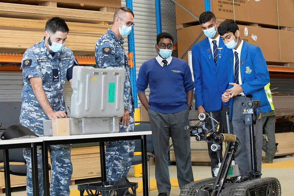 Leading Aircraftman Chris Carrigan, left, and Leading Aircraftman Jordan Hopkins demonstrate a vehicle used to detect Improvised Explosive Devices to Patrician Brothers students Amarjith Ajith, Agam Gujral and Damien Sinha, Photo: Corporal Kylie Gibson