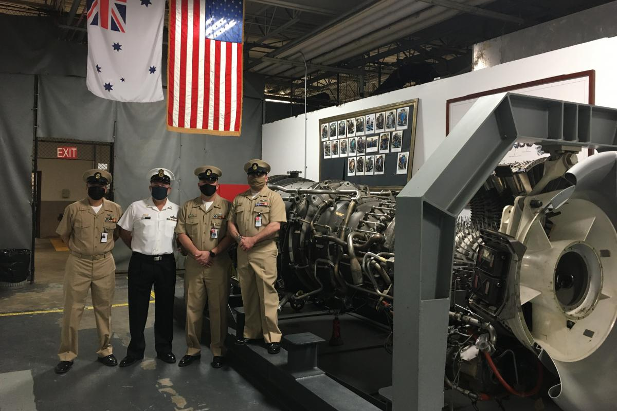 Chief Petty Officer John Bywater, second from left, with South East Regional Maintenance Centre service personnel alongside the gas turbine shop trainer engine at the Naval Station in Mayport, Florida.