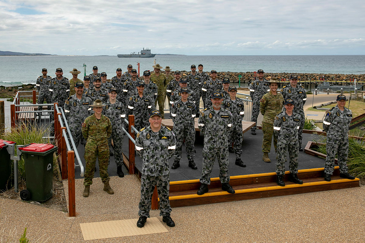 HMAS Choules Commanding Officer, Commander Ben Reilly, with his crew members prior to an announcement that Mallacoota in Victoria was the ship's new ceremonial homeport.