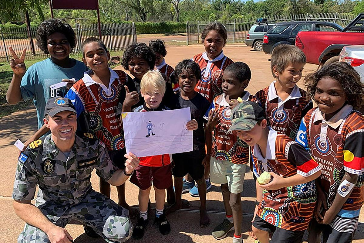 HMAS Coonawarra Officer Lieutenant Matt Dobrincic with students from Borroloola Primary School during Anzac Day community engagement.