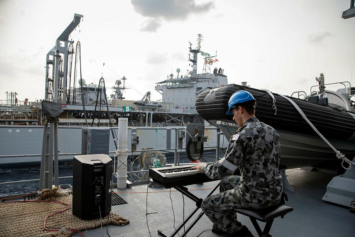 Able Seaman Xavier Riddell plays the keyboard during a replenishment at sea with HMAS Sirius in the Bay of Bengal. Photo: Leading Seaman Thomas Sawtell