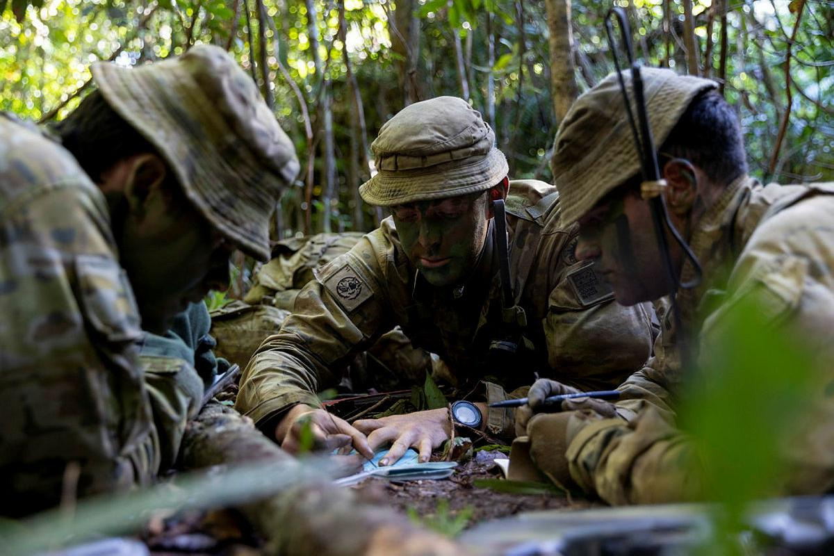 Lieutenant David Adams, centre, from the 6th Battalion, Royal Australian Regiment, briefs Major David Hodge, left, at the Combat Training Centre - Jungle Training Wing, Tully, Queensland. Photo: Corporal Brodie Cross