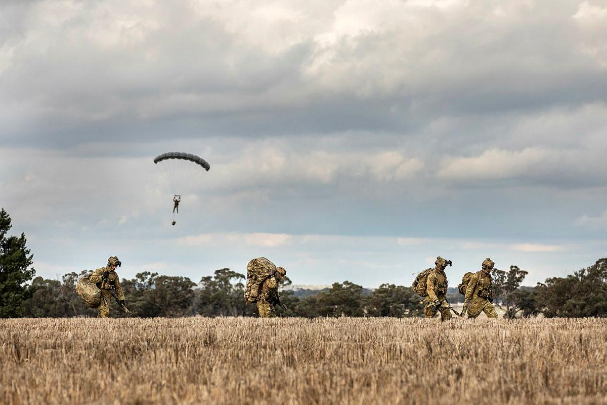Soldiers from 2 Commando Regiment depart the drop zone after parachuting into crop fields in Temora, NSW. Photo: Sergeant Janine Fabre