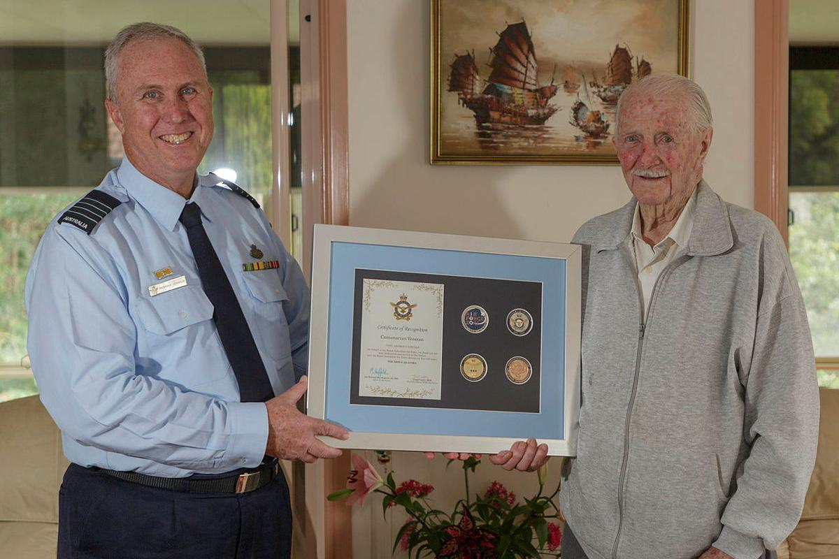 Senior Australian Defence Force Officer for RAAF Base Williamtown Group Captain Anthony Stainton presents George Lincoln an Air Force centenary memento. Photo: Sergeant David Gibbs