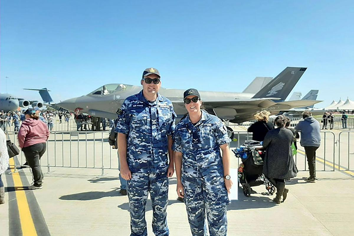 Leading Aircraftman Will Pinkerton and Leading Aircraftwoman Kate King stand in front of an F-35A Lightning II aircraft at Avalon Air Show, Victoria.