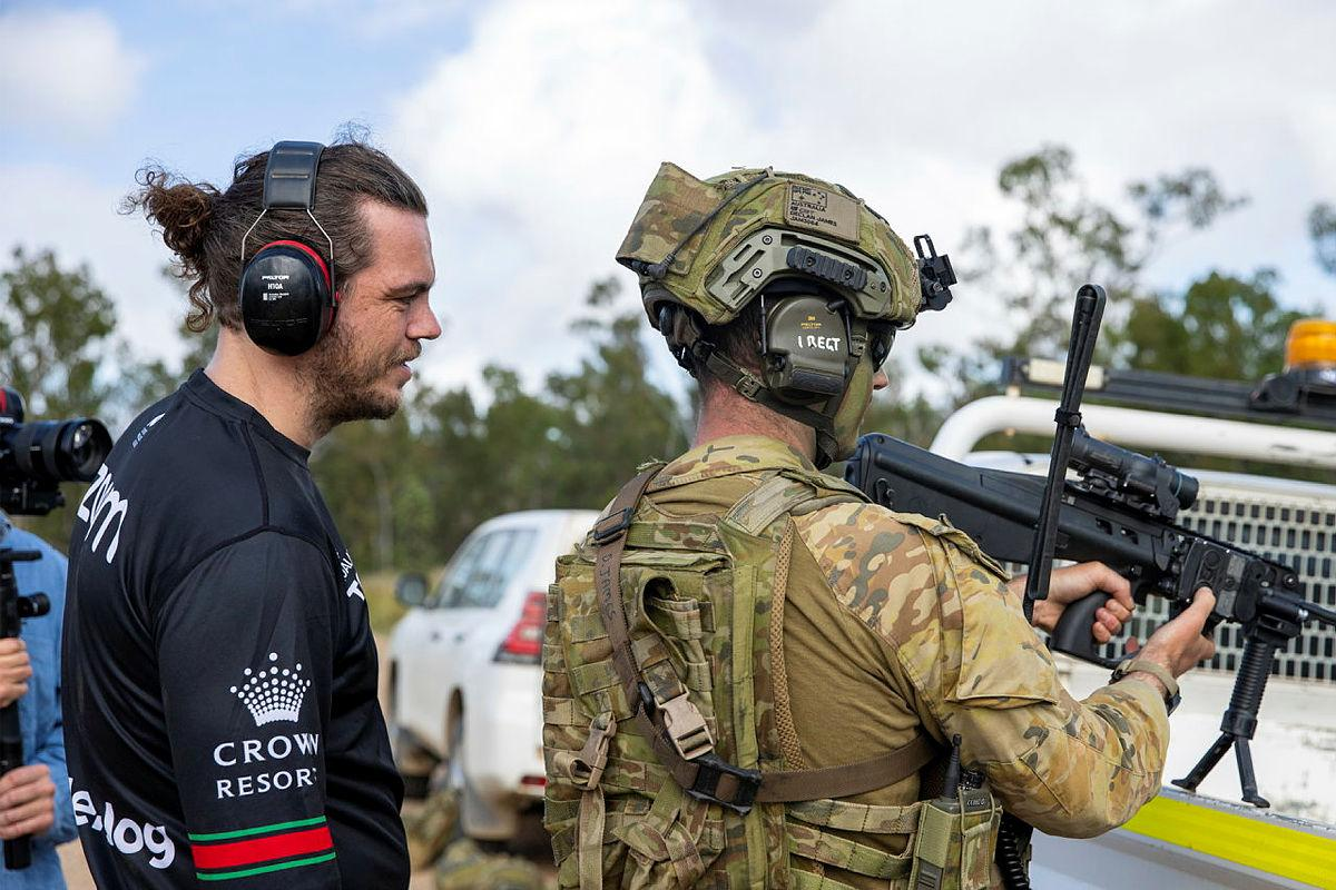 Captain Declan James explains the workings of an EF88 Austeyr Rifle to former South Sydney Rabbitoh player Ethan Lowe during his visit to Shoalwater Bay Training Area, Queensland. Photo: Corporal Nicole Dorrett