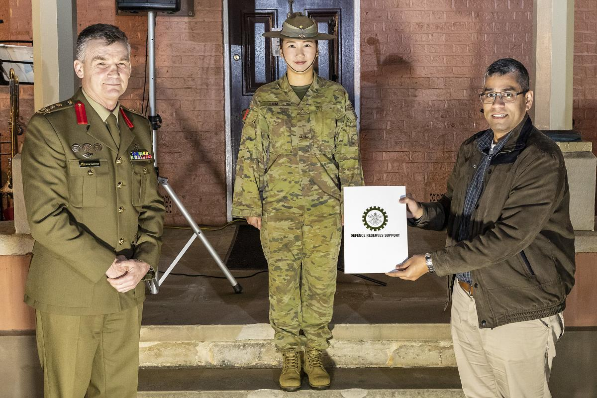 Reservist Private Izzy Kim, centre, with her civilian employer, manager Digital Analytics and Business Enablement at HCF Australia Hari Somayajula receiving a certificate of appreciation from Brigadier Mick Garraway. Photo: Corporal Dan Pinhorn