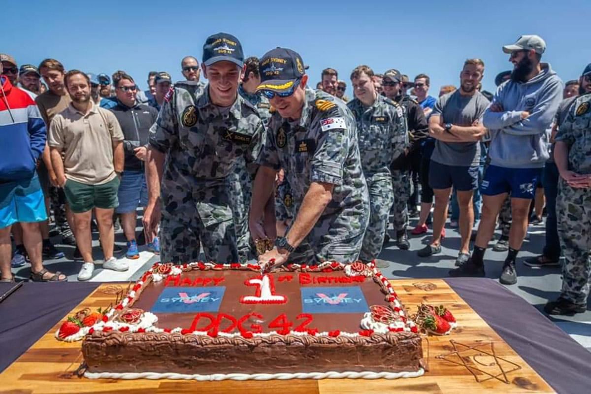 HMAS Sydney's youngest crew member Seaman Sebastien Schultz, left,  and Commanding Officer Commander Edward Seymour cut a cake to mark the first anniversary of the ship's commissioning into the Navy.