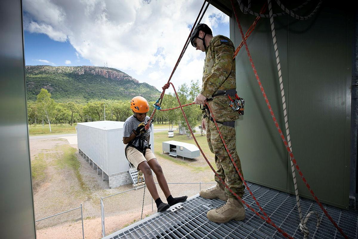 Lance Corporal Jordan Blake assists a participant of the Townsville Fire Youth Engagement Program during resilience activities at Lavarack Barracks. Photo: Corporal Brandon Grey