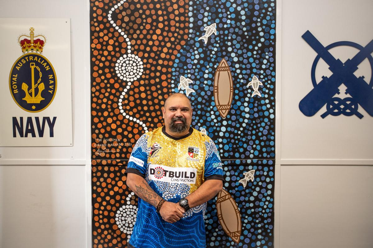 Indigenous artist Garry Purchase with one of his murals.Photo: Able Seaman Lucinda Allanson