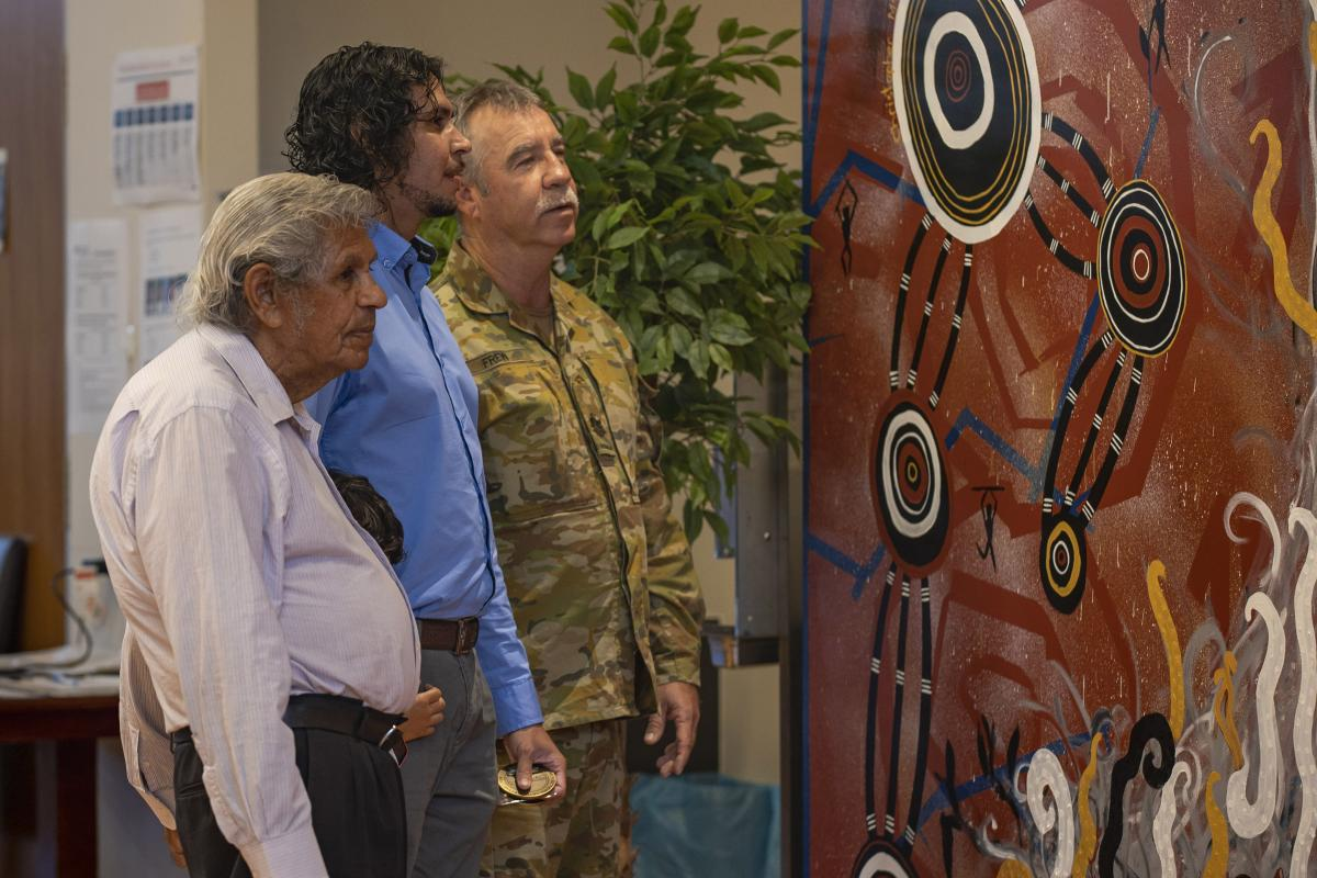Indigenous Elder Uncle Desmond Sandy, left, artist Christopher McGregor-Sandy and Warrant Officer Class One Geoffrey Frew view the painting presented to the sergeants' mess at Gallipoli Barracks. Photo: Corporal Nicole Dorrett