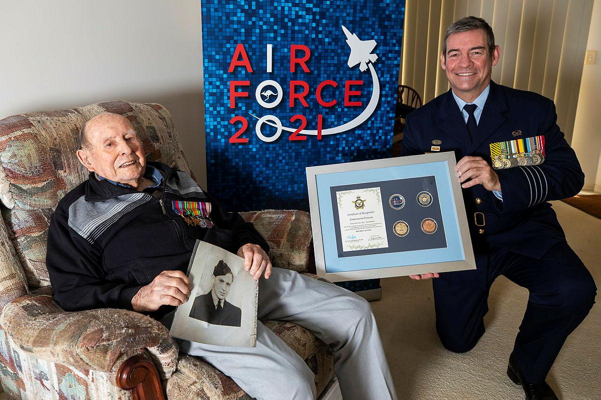 Senior ADF Officer RAAF Base Amberley Group Captain Iain Carty presents Air Force veteran Bill Heatherill with an Air Force 2021 commemorative memento in celebration of his 100th birthday. Photo: Corporal Jesse Kane