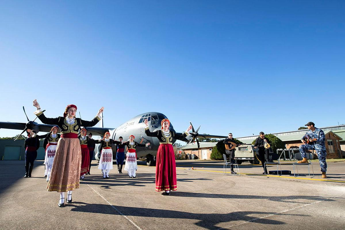 Dancers from the Cretan Association of Sydney perform in front of a C-130J Hercules as No. 37 Squadron avionics technician Leading Aircraftman Yianni Skoulakis, right, plays the laouto at RAAF Base Richmond. Photo: Corporal David Said