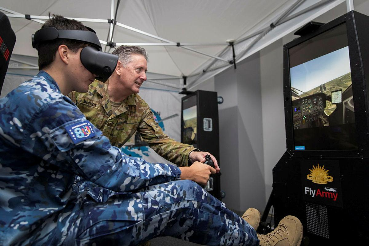Major David McEvoy instructs an Air Force cadet flying a Sikorsky S-76 helicopter, using the Army helicopter flight simulator during the Women in Defence Careers Expo held in Darwin. Photo: Private Jacob Joseph