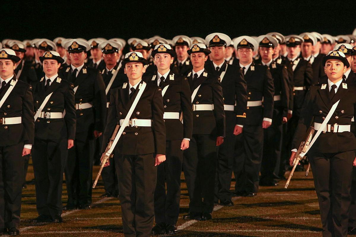 Graduates of the New Entry Officers Course 64 parade stand at attention during a ceremonial sunset on the evening before their graduation at HMAS Creswell, Jervis Bay. Photo: Able Seaman Leon Dafonte Fernandez