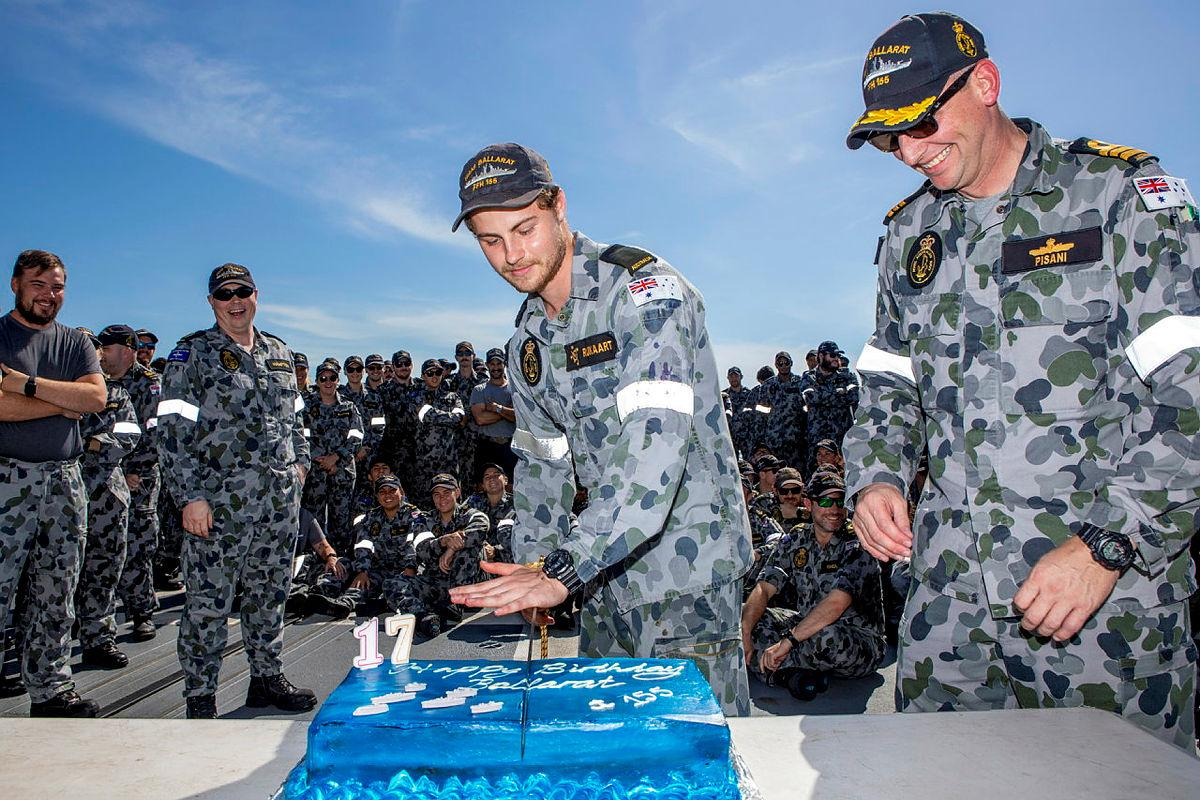 Commanding Officer Ballarat Commander Antony Pisani, right, with the youngest crew member Seaman Christiaan Rijkaart during the cutting of the ship's birthday cake at sea. Photo: Leading Seaman Ernesto Sanchez