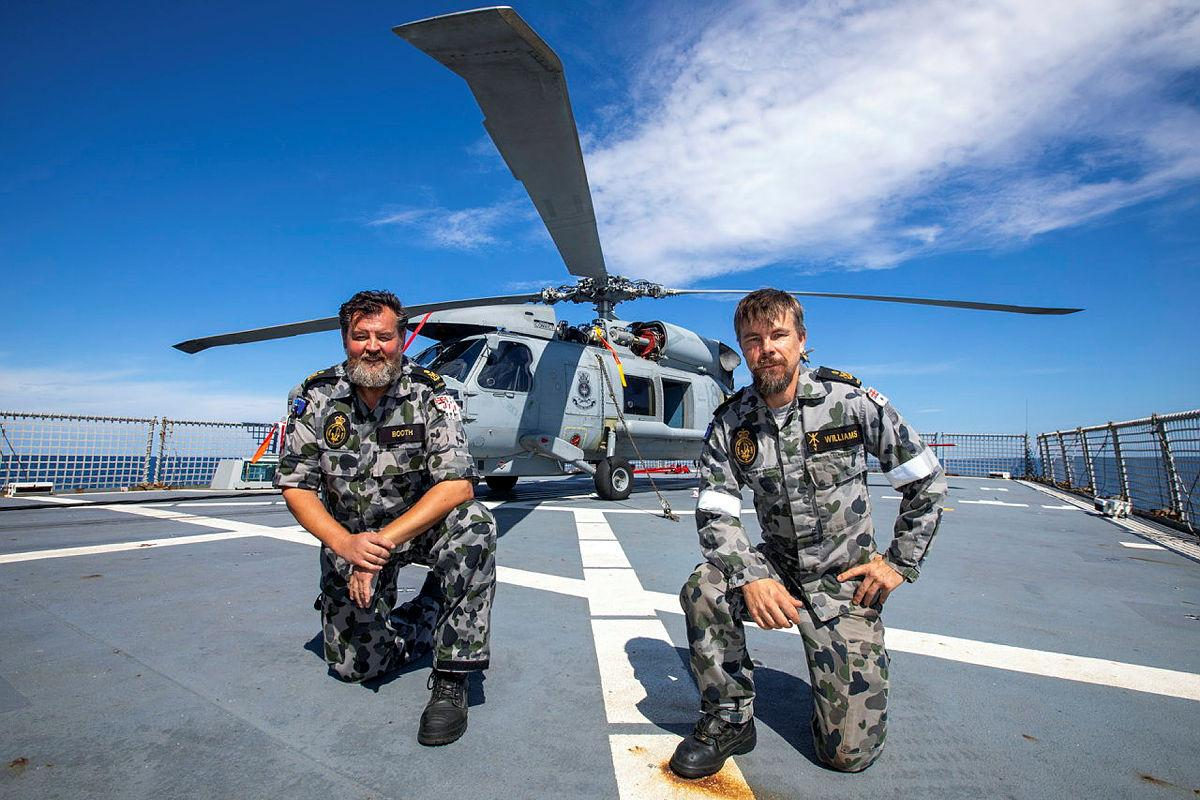Petty Officers Andrew Booth, left, and Patrick Williams, from 816 Squadron's Flight 3 crew, with HMAS Ballarat's embarked MH-60R. Photo: Leading Seaman Ernesto Sanchez