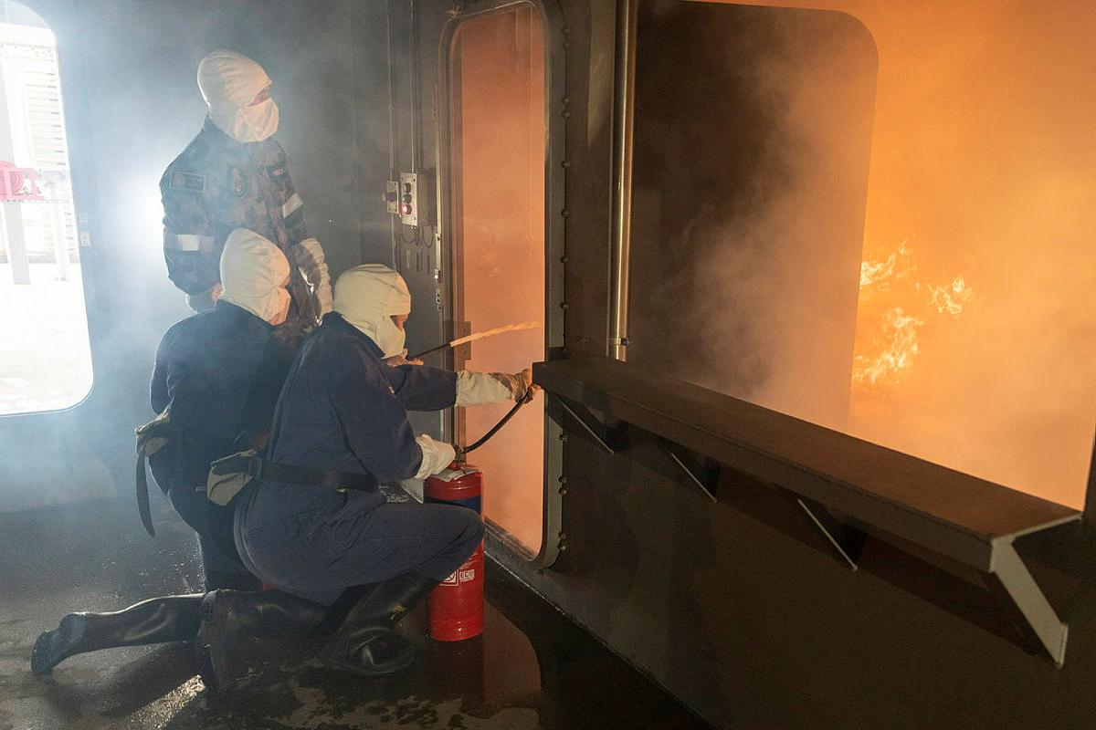 Participants in the Defence Work Experience Program are instructed how to use fire extinguishers in the School of Ship Safety and Survivability fire simulator during a visit to HMAS Cerberus. Photo: Leading Seaman James McDougall