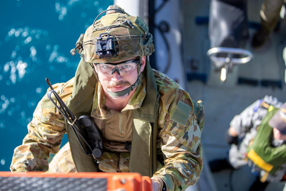 An Australian Army soldier climbs aboard HMAS Ballarat from a Rigid-Hulled Inflatable Boat during joint pre-landing force training, off the coast of Queensland, during Exercise Talisman Sabre 2021. Photo:  LSIS Ernesto Sanchez