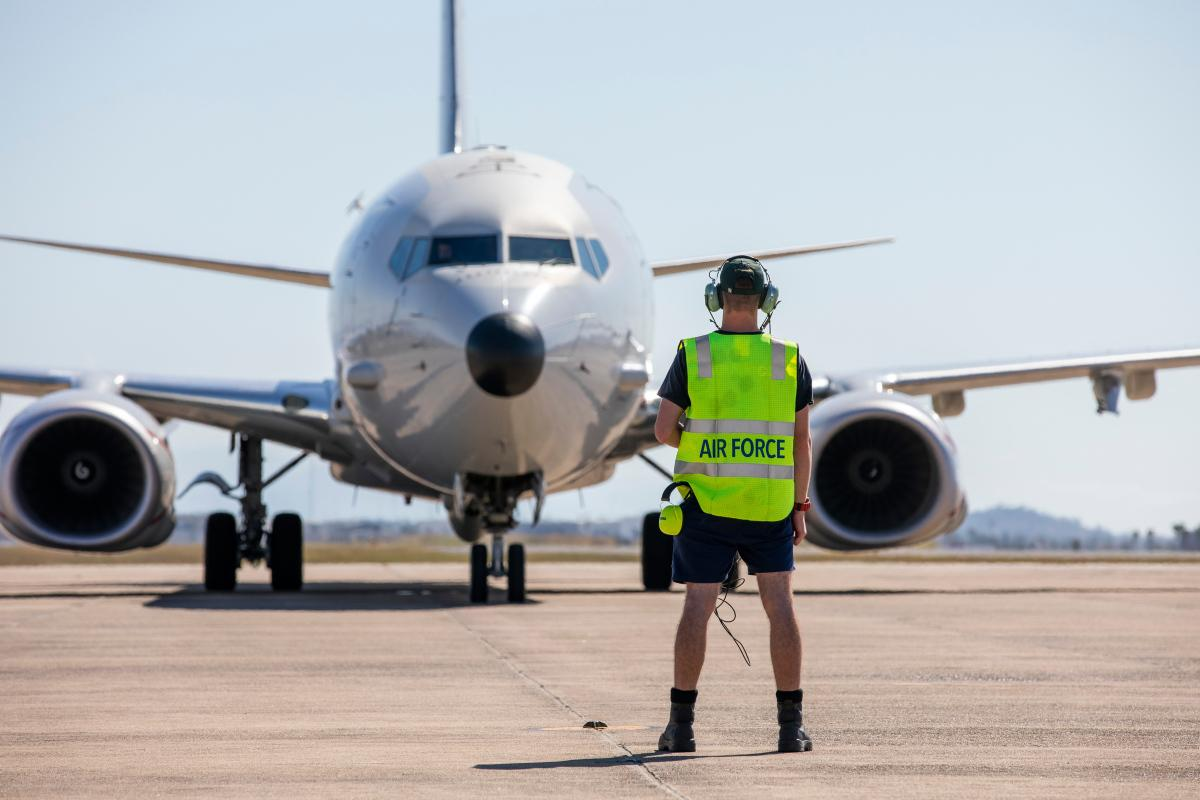 A Royal Australian Air Force Avionics Technician guides a P-8A Poseidon aircraft into position, as it prepares to depart RAAF Base Townsville in Queensland, during Exercise Talisman Sabre 2021. Photo: LACW Emma Schwenke