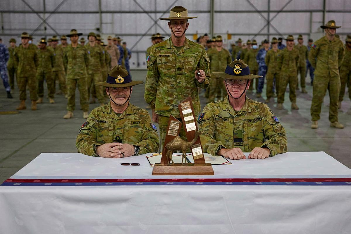 Rear Admiral Michael Rothwell, left, and Air Commodore David Paddison, right, after signing the Transfer of Authority for Command of Joint Task Force 633, witnessed by Warrant Officer Class One Mark Retallick. Photo: Sergeant Andrew Sleeman