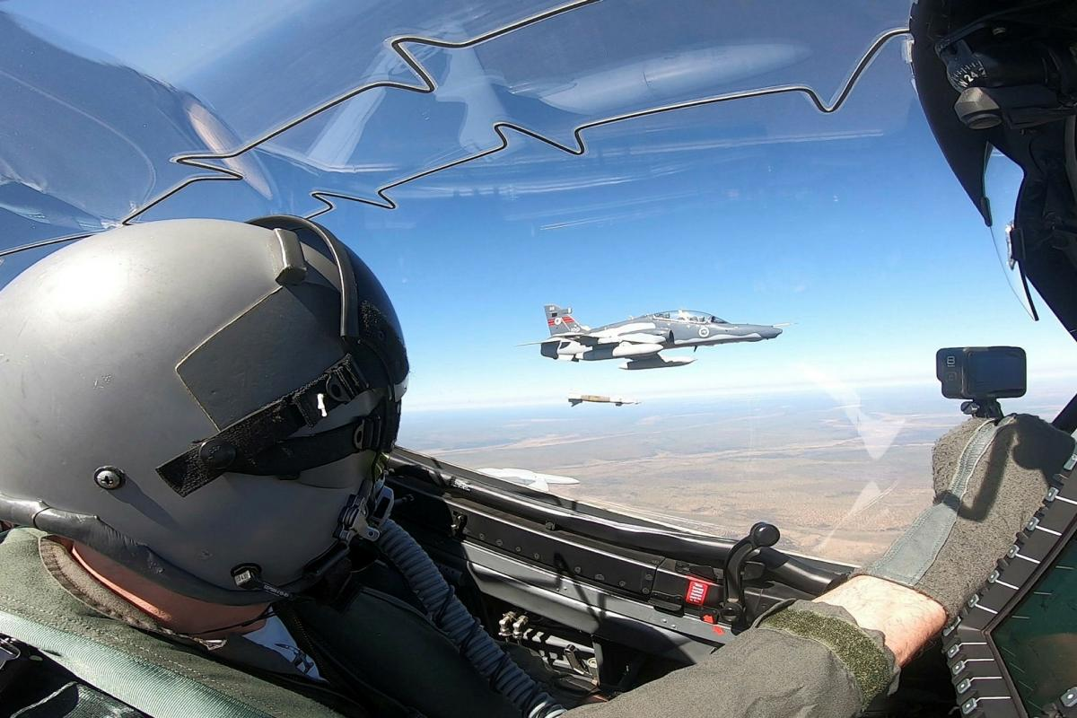 A Hawk 127 lead-in fighter pilot from No. 79 Squadron watches as a Hawk 127 from No. 76 Squadron releases a GBU-12 laser-guided Bomb over Delamere Air Weapons Range, Northern Territory.