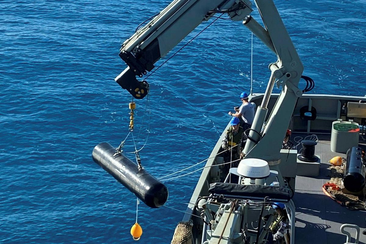 Personnel from HMAS Melville use a crane to lay an inert dummy mine off the coast of Queensland as part of Exercise Talisman Sabre.
