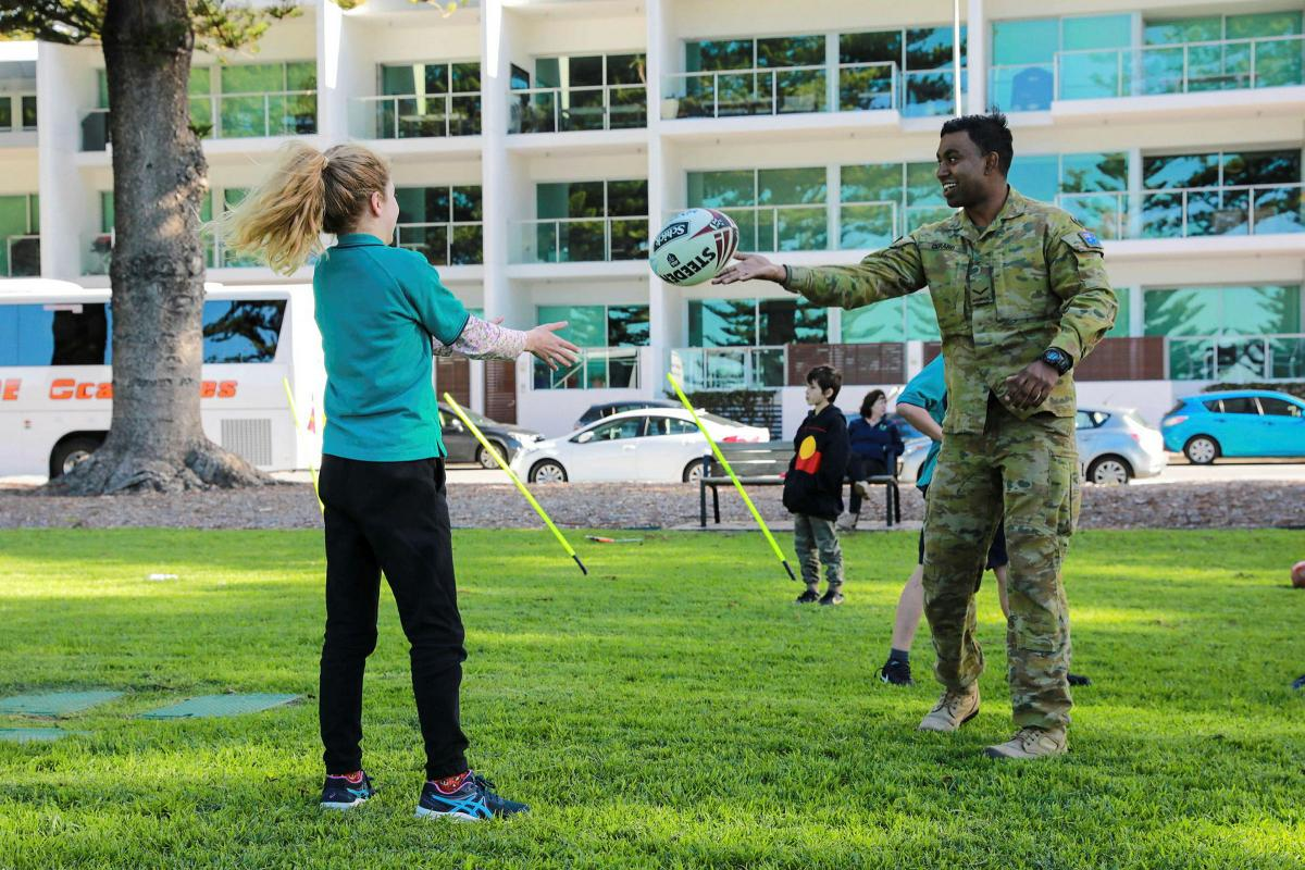 Lance Corporal Aaron Gerard, of the 7th Battalion, Royal Australian Regiment, plays football with a member of the Victor Harbor community during NAIDOC Week celebrations. Photo: Private Saar Hayon