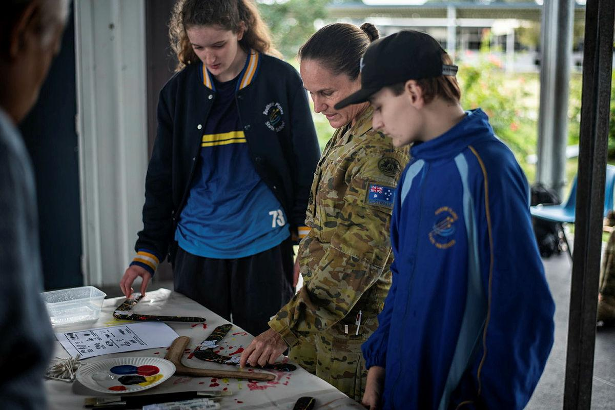 Warrant Officer Class One Kelly Hammant instructs students from Redbank Plains State High School how to paint boomerangs in traditional styles. Photo: Private Jacob Hilton