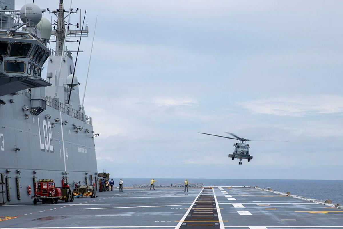 An MH-60R conducts deck landing training on HMAS Canberra as the ship sails through the Coral Sea to take part in the Large Scale Global Exercise 21. Photo: Leading Seaman Nadav Harel