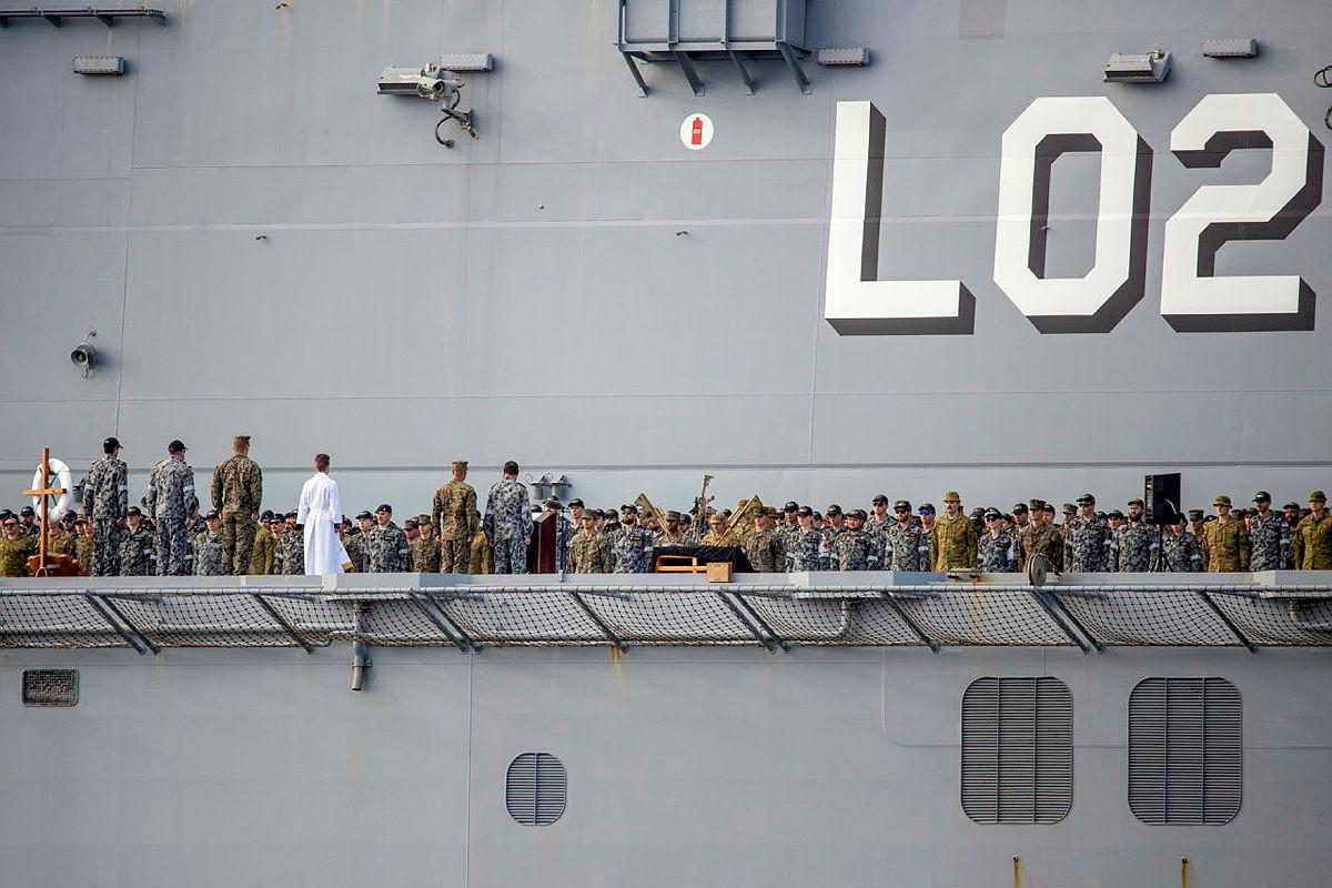 The ship's company of HMAS Canberra commemorates the 79th anniversary of the Battle of Savo Island on the flight deck while at sea in the Western Pacific. Photo: Leading Seaman Ernesto Sanchez