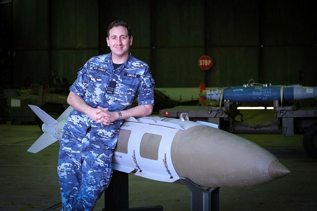 Defence Explosive Ordnance Training School instructor Flight Lieutenant Ben Lindsay with a teaching aid, a 2000-pound joint direct attack munition.