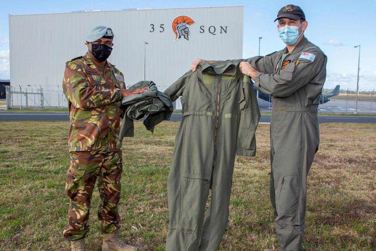 Captain Randall Hepota of the Papua New Guinea Defence Force is presented with flying clothing during his visit to No. 35 Squadron at RAAF Base Amberley by Squadron Leader Robert Crawford. Photo: Sergeant Peter Borys