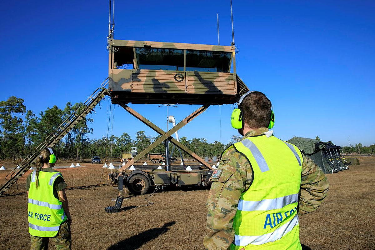 Leading Aircraftwoman Rebecca Hay and Corporal Thomas Geraghty raise the transportable air operations tower at RAAF Base Scherger. Photo: Corporal Brett Sherriff