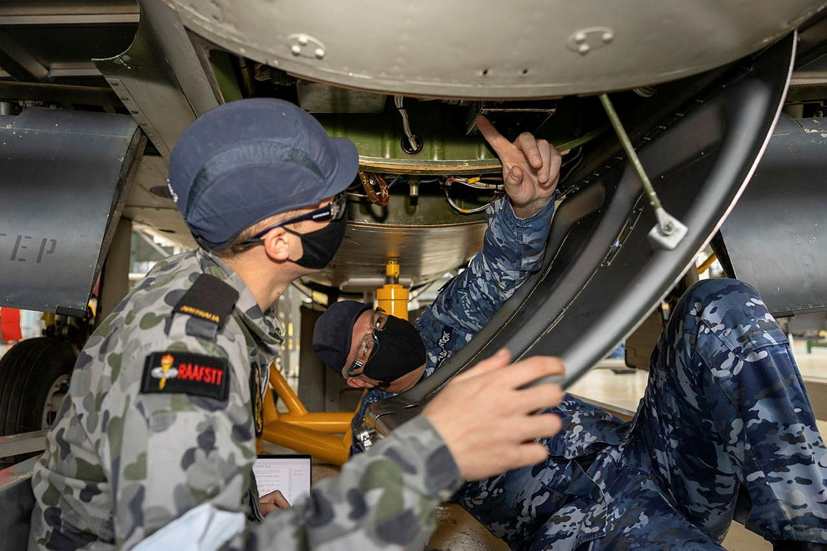 Corporal Andrew Ashbrook, right, helps avionics technician trainee Seaman William Cook to identify, recover and install a faulty voltage regulator.