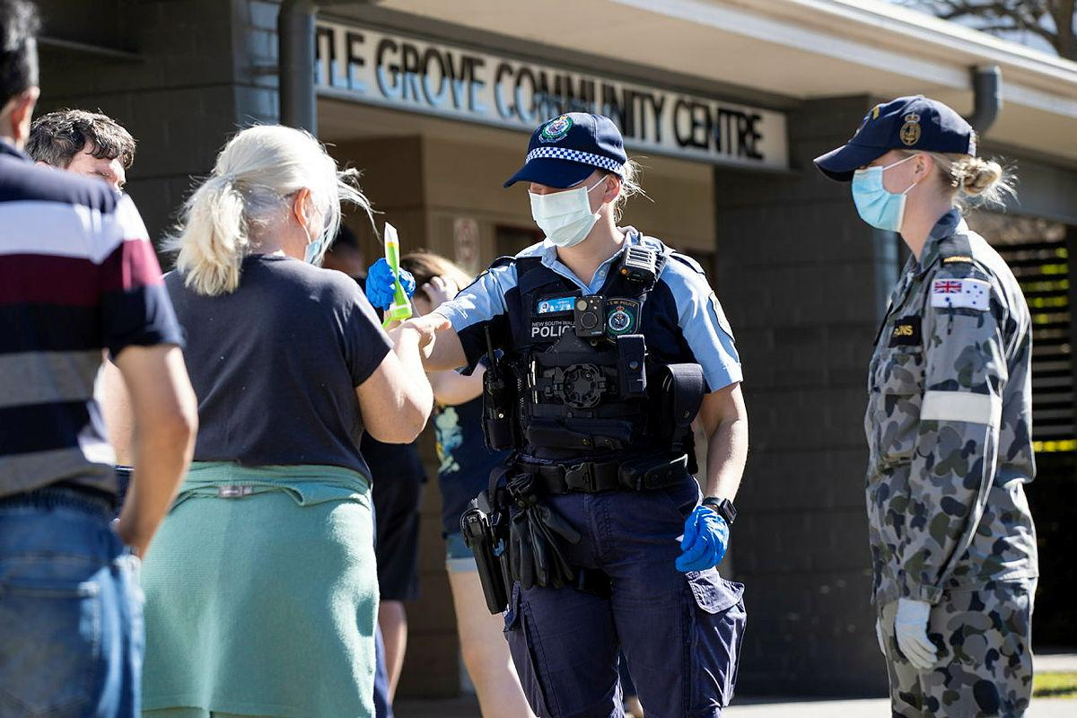 NSW Police Constable Megan Green and Seaman Jordan Parsons hand out sunscreen to civilians waiting in line for a COVID-19 test at the Wattle Grove Community Centre. Photo: Corporal Dustin Anderson