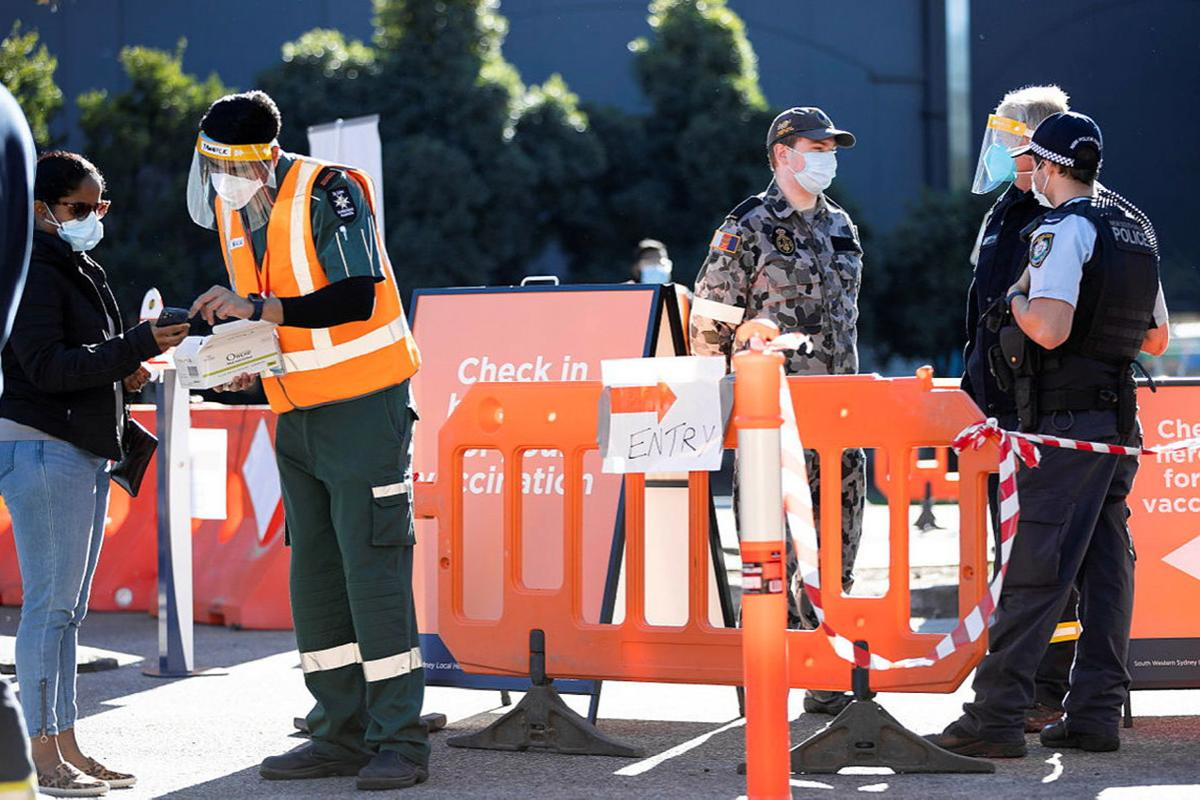 Seaman Nicholas Hopkins talks with members of the NSW Police and NSW Rural Fire Service at the Prariewood Community Centre Vaccination Hub in Fairfield, Sydney. Photo: Corporal Dustin Anderson