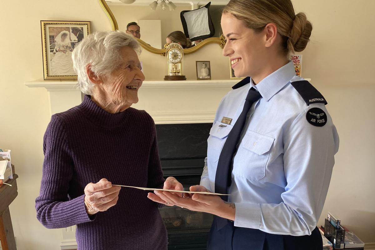 Shirley Stone shows Aircraftwoman Cassandra Field her World War II training certificate during the presentation in Adelaide.