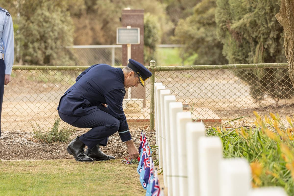 Air Commodore Ross Bender lays a sprig of rosemary at one of the grave sites during a commemoration ceremony at Mallala War Cemetery. Photo: Leading Aircraftman Stewart Gould