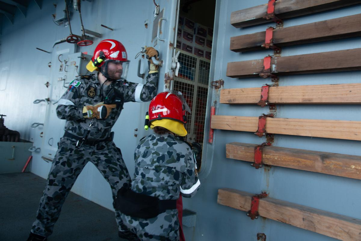 Able Seaman Paul Murra and Able Seaman Lydia Monk participate in a fire hose drill during damage control training on board HMAS Sirius.
