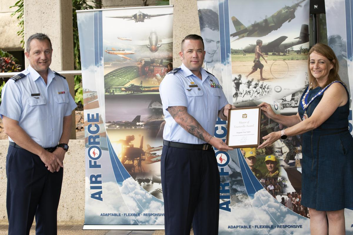 Senior ADF officer at RAAF Base Townsville Wing Commander Mathew Green watches on as Sergeant Tory Tipler is presented with his award by Townsville Mayor Jenny Hill.