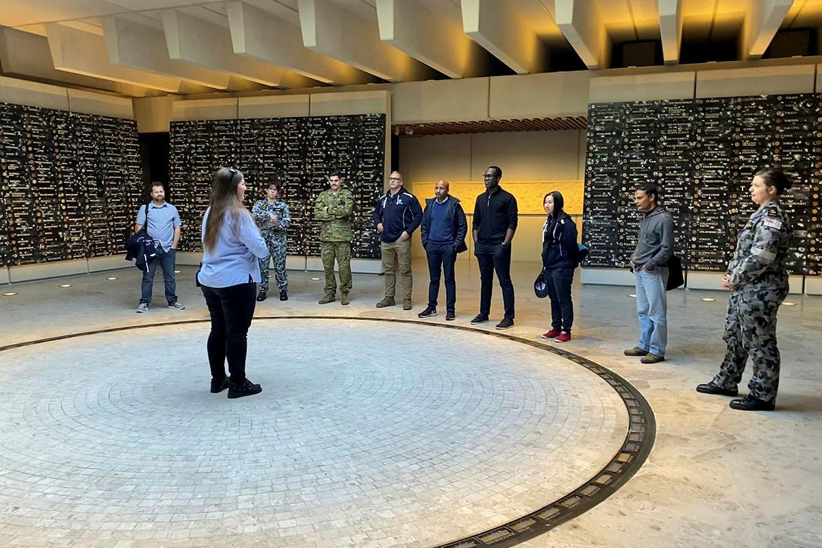 Ashleigh Taylor, from the AnzacMemorial, guidesADF Cyber Gap Program participants around the memorial in Sydney's Hyde Park.