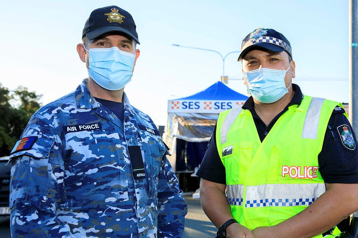 Flying Officer Brett Smith talks with his mate and former colleague Senior Constable Jared Cowan at the Gold Coast Highway police checkpoint. Photo: Corporal Brett Sherriff