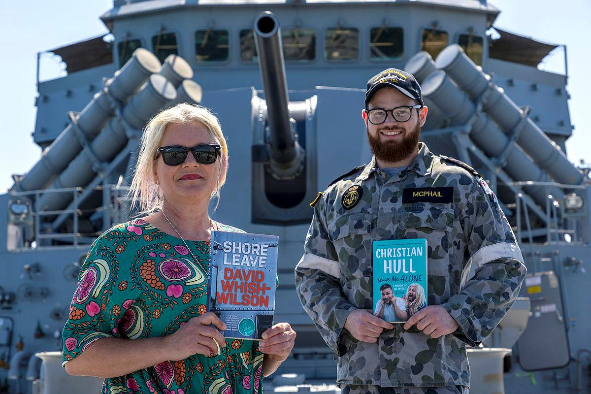 Owner of My Little Bookshop Kerry Ridley with Leading Seaman James McPhail on board HMAS Warramunga at Fleet Base West. Photo: Petty Officer Yuri Ramsey