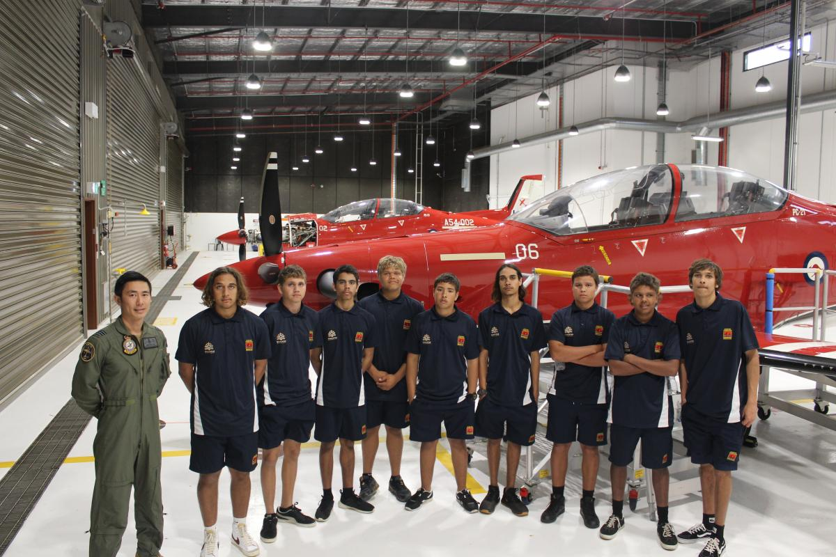 Qualified flying instructor with No. 2 Flying Training School Flight Lieutenant Jonathan Lee and students from Clontarf Academy in front of a Pilatus PC-21 aircraft at RAAF Base Pearce.
