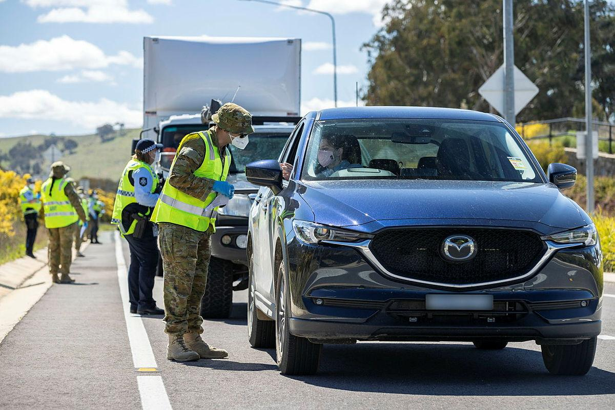 Lance Corporal Mancell Laidler, of Joint Task Group 629.9, inspects the licence of a motorist at the ACT Federal Highway border-control point during Operation COVID-19 Assist. Photo: Corporal Jarrod McAneney